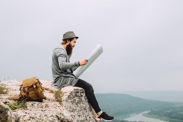 Młody brodaty turysta siedzi na wysokiej skale. i trzyma mapę