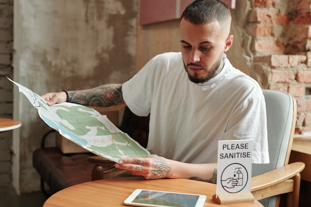 Młody brodaty turysta z tatuażami siedzi przy stole w hotelowym lobby i znajduje miejsce na mapach online i papierowych