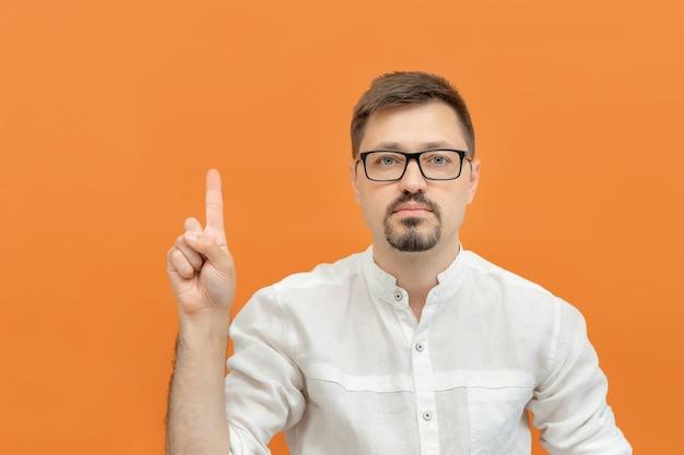 Młody brodaty zamyślony mężczyzna w okularach wskazujący palcem w górę wskazuje, aby skopiować kosmiczną pomarańczę