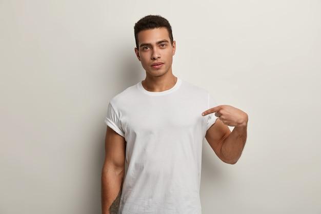 Młody brunet mężczyzna ubrany w białą koszulkę