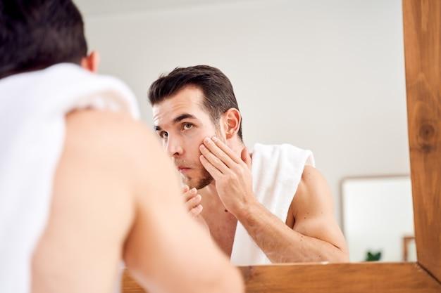 Młody brunet myje twarz i stoi z ręcznikiem na ramionach przed lustrem w łazience