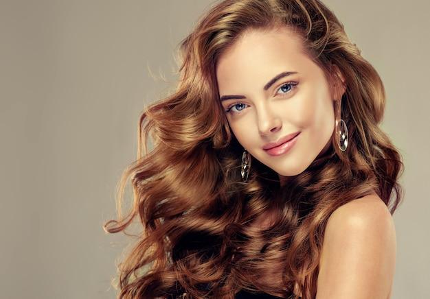 Młody brunet piękny model z długimi kręconymi włosami. piękny model o długich, gęstych, kręconych włosach