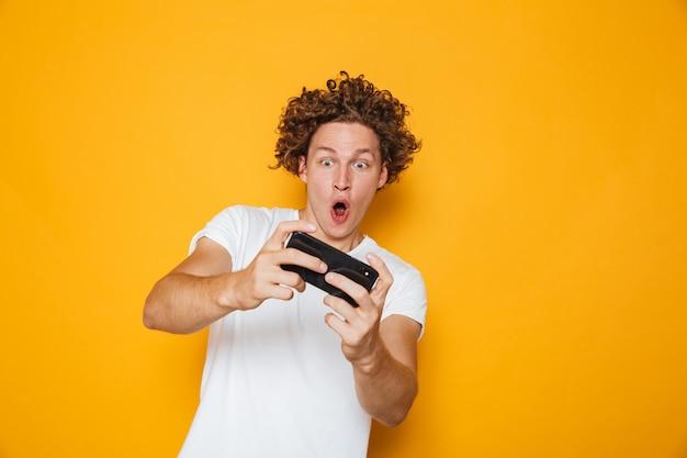 Młody brunetka facet w dorywczo t-shirt, grając w gry wideo online za pomocą telefonu komórkowego