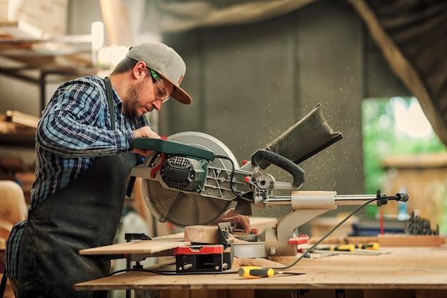 Młody brunetka mężczyzna w ubraniach roboczych piły z piłą tarczową drewnianą deskę