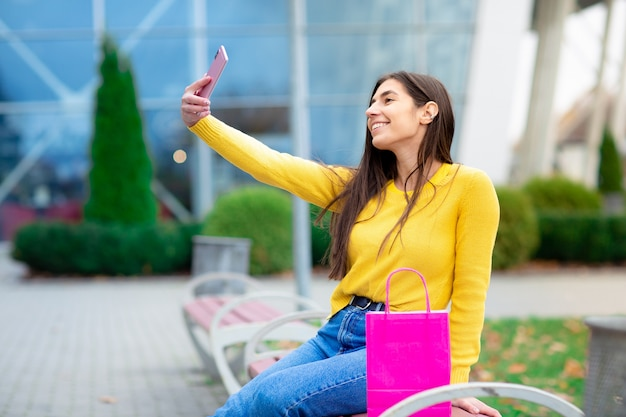 Młody brunetki kobiety siedzieć plenerowy na ławce z różowymi torba na zakupy i robić selfies. kobieta ubrana w żółty sweter