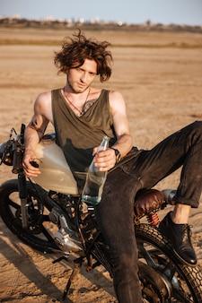 Młody brutalny mężczyzna leżący na motocyklu na pustyni i trzymający szklaną butelkę wody water