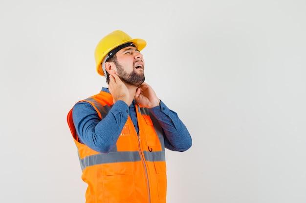 Młody budowniczy cierpiący na ból szyi w koszuli, kamizelce, kasku i wygląda na wyczerpanego, widok z przodu.