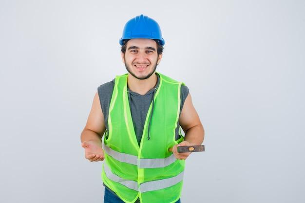 Młody budowniczy mężczyzna trzyma młotek podczas rozkładania dłoni w mundurze odzieży roboczej i wygląda radośnie, widok z przodu.