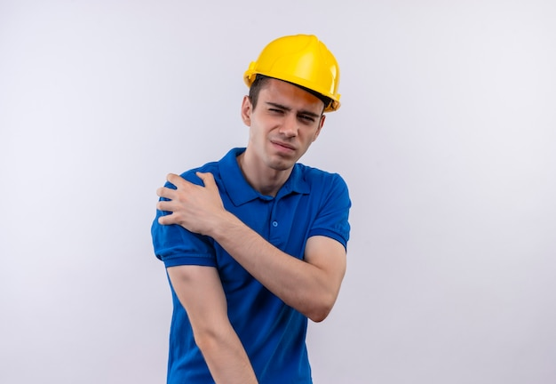 Młody budowniczy mężczyzna ubrany w mundur budowlany i hełm ochronny robi nieszczęśliwą twarz i cierpi z powodu bólu