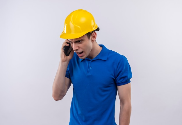 Młody budowniczy mężczyzna ubrany w mundur konstrukcyjny i kask ochronny ze złością rozmawia przez telefon