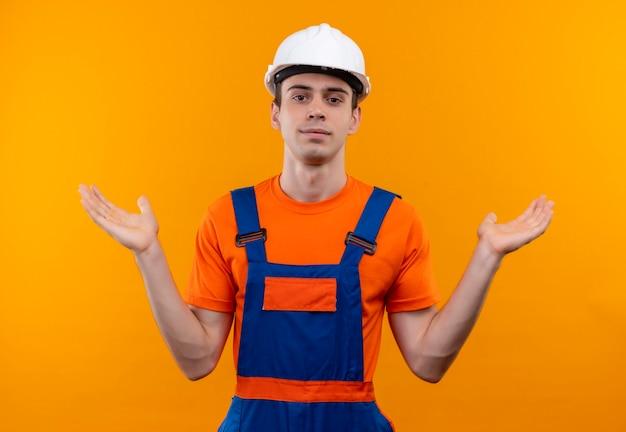 Młody budowniczy mężczyzna ubrany w mundur konstrukcyjny i kask podnosi ręce