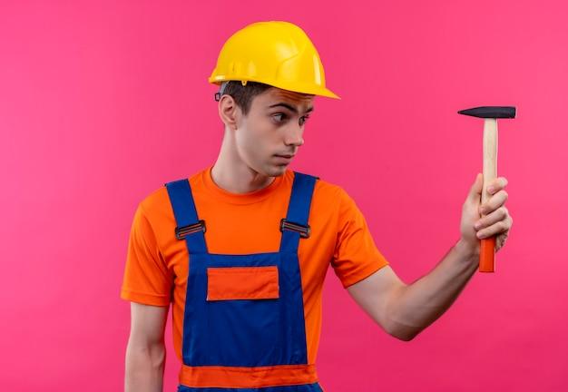 Młody budowniczy mężczyzna ubrany w mundur konstrukcyjny i kask posiada młotek