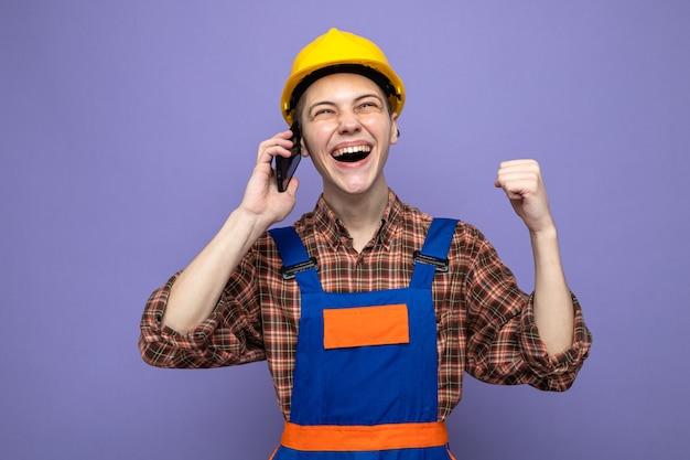 Młody budowniczy mężczyzna ubrany w mundur mówi przez telefon odizolowany na fioletowej ścianie