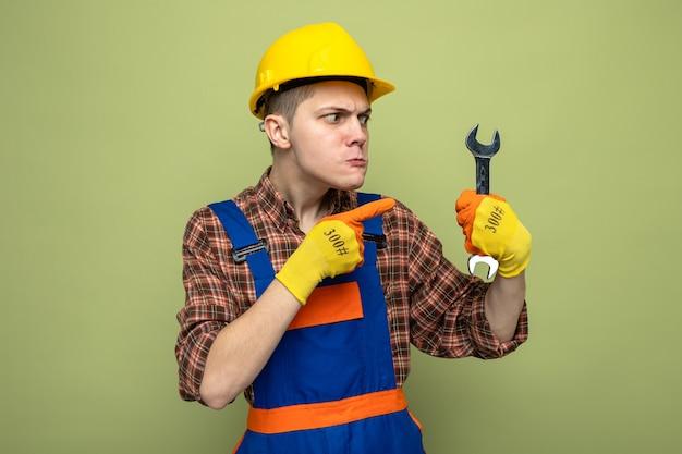 Młody budowniczy mężczyzna ubrany w mundur z rękawiczkami trzymającymi i wskazujący na klucz płaski odizolowany na oliwkowozielonej ścianie
