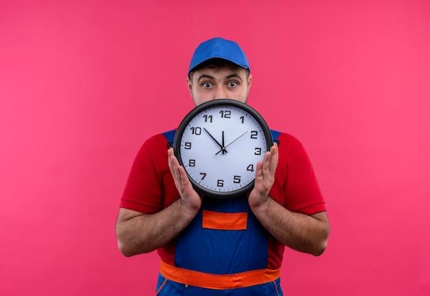 Młody budowniczy mężczyzna w mundurze budowlanym i czapce trzyma zegar ścienny, ukrywając za nim twarz, zerkając na zaskoczonego