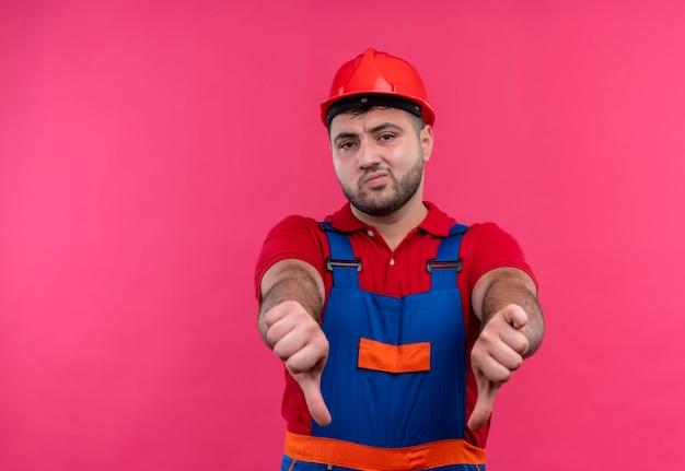 Młody budowniczy mężczyzna w mundurze budowlanym i hełmie ochronnym pokazując kciuki w dół obiema rękami niezadowolony