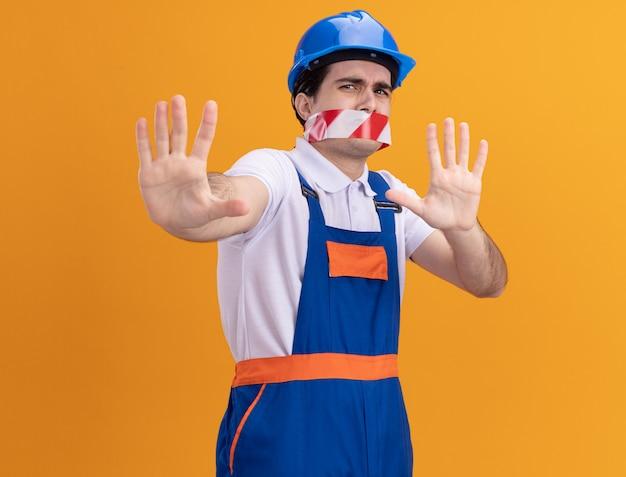 Młody budowniczy mężczyzna w mundurze budowlanym i hełmie ochronnym z taśmą owiniętą wokół ust, przestraszony, trzymając się za ręce, wykonując gest obrony, stojąc nad pomarańczową ścianą