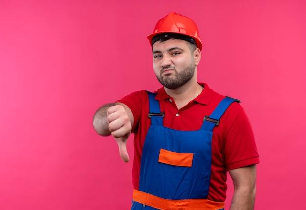Młody budowniczy mężczyzna w mundurze budowlanym i kasku ochronnym, niezadowolony, pokazując kciuk w dół