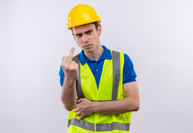 Młody budowniczy mężczyzna w mundurze budowlanym i kasku ochronnym pokazuje kurwa zły