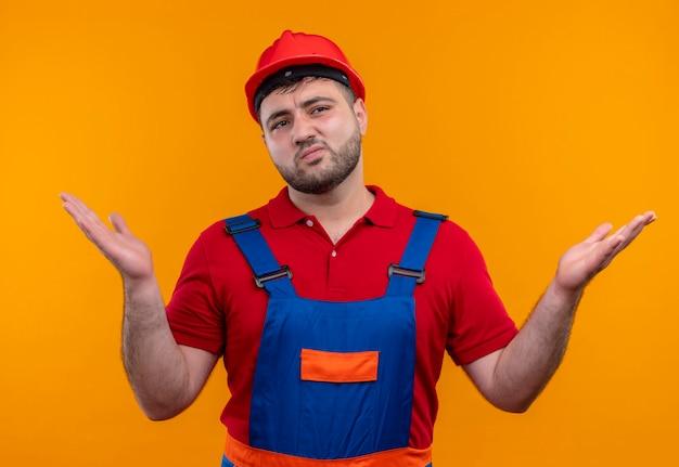Młody budowniczy mężczyzna w mundurze budowlanym i kasku ochronnym wyglądający na zdezorientowanego, rozkładając ręce na boki, nie mając odpowiedzi