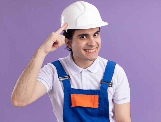 Młody budowniczy mężczyzna w mundurze budowlanym i kasku ochronnym z pewnym wyrazem twarzy na inteligentnej twarzy, uśmiechnięty, wskazujący palcem wskazującym na swoją świątynię, skupiony na zadaniu