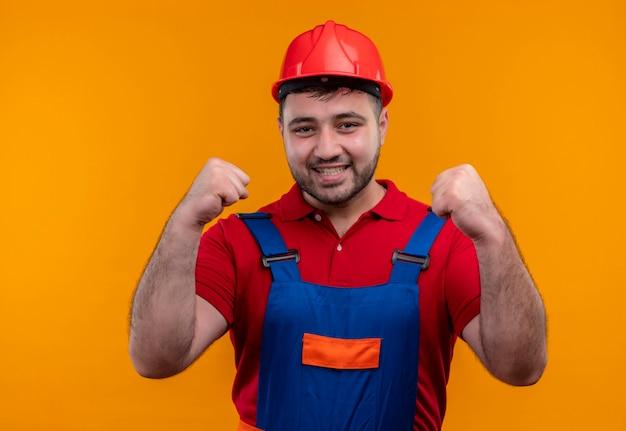 Młody budowniczy mężczyzna w mundurze budowlanym i kasku ochronnym zaciskając pięści szczęśliwy i wyszedł, ciesząc się swoim sukcesem