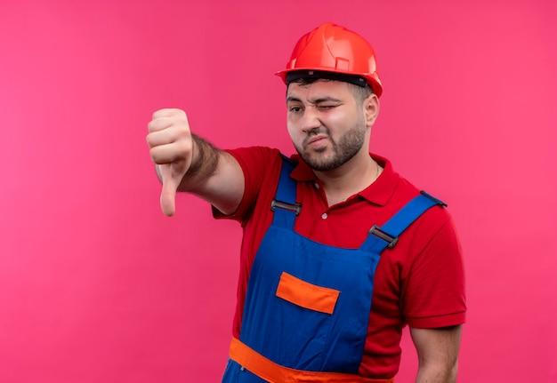 Młody budowniczy mężczyzna w mundurze konstrukcyjnym i hełmie ochronnym pokazując niezadowolony kciuk w dół