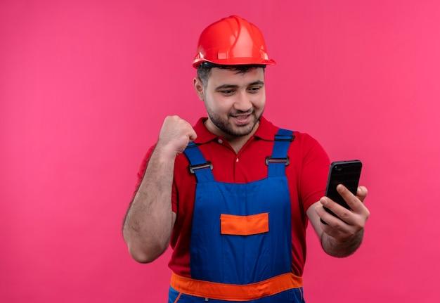 Młody budowniczy mężczyzna w mundurze konstrukcyjnym i kasku ochronnym, patrząc na ekran, jest smartfonem zaciskającym pięść szczęśliwy i wyszedł, ciesząc się swoim sukcesem