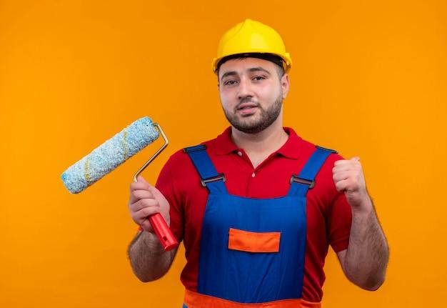 Młody budowniczy mężczyzna w mundurze konstrukcyjnym i kasku ochronnym, trzymając wałek do malowania zaciskając pięść jak zwycięzca