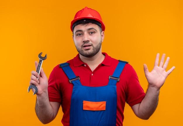 Młody budowniczy mężczyzna w mundurze konstrukcyjnym i kasku ochronnym trzymający klucz wyglądający na zdezorientowanego, rozkładający ręce na boki, mający wątpliwości