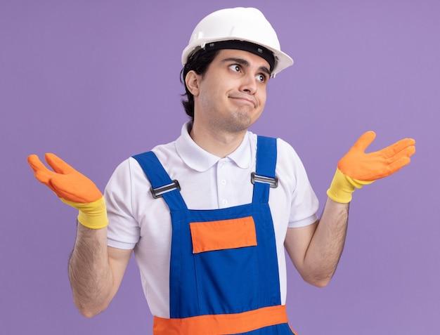 Młody budowniczy mężczyzna w mundurze konstrukcyjnym i kasku ochronnym w gumowych rękawiczkach patrząc z przodu, zdezorientowany i niepewny, z podniesionymi rękami i bez odpowiedzi stojąc nad fioletową ścianą