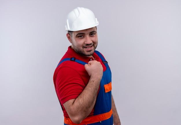 Młody budowniczy mężczyzna w mundurze konstrukcyjnym i kasku ochronnym zaciskając pięść szczęśliwy i wyszedł, ciesząc się swoim sukcesem