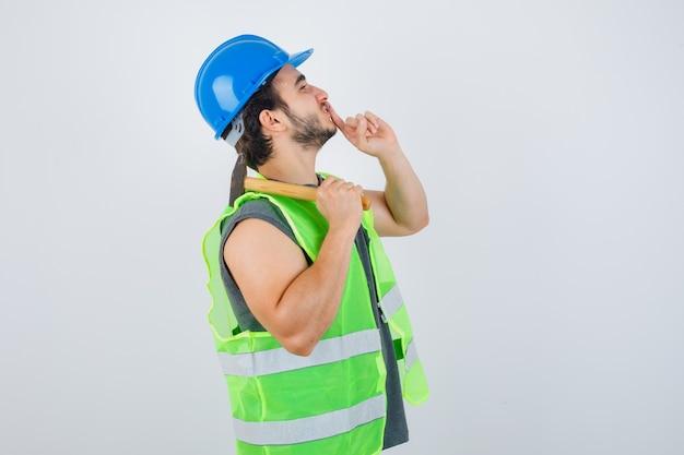 Młody budowniczy mężczyzna w mundurze odzieży roboczej trzymając młotek na ramieniu, pokazując gest ciszy i patrząc uważnie z przodu.