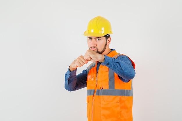 Młody budowniczy stojący w pozie boksera w koszuli, kamizelce, kasku i patrząc poważnie. przedni widok.