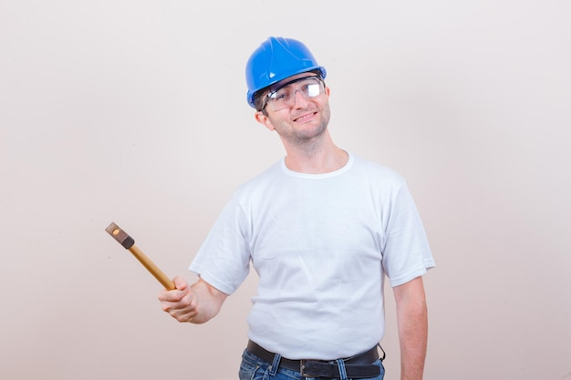 Młody budowniczy trzyma młotek w koszulce, dżinsach, kasku i wygląda wesoło