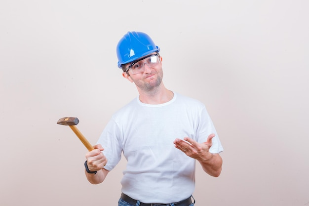 Młody budowniczy w koszulce, dżinsach, hełmie pokazującym młotek i wyglądającym na rozczarowanego