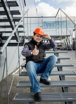 Młody budowniczy w pomarańczowym kasku siedzi na metalowych schodach i pokazuje kciuk w górę thumb