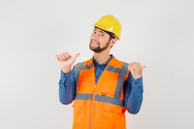 Młody budowniczy wskazujący kciuki do tyłu w koszuli, kamizelce, kasku i wyglądający jowialnie. przedni widok.