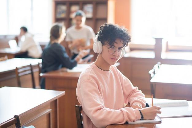 Młody, bystry student collegu patrzy na ciebie przez okulary, słuchając muzyki w słuchawkach i pracując przy biurku