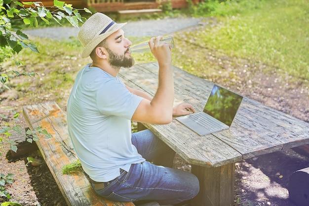 Młody całkiem kaukaski mężczyzna siedzi na drewnianym stole w lesie i wody pitnej podczas pracy na komputerze.