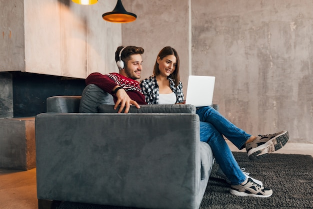 Młody całkiem szczęśliwy uśmiechnięty mężczyzna i kobieta siedzą w domu zimą, patrząc w laptopa, słuchając słuchawek, studenci studiujący online, para w czasie wolnym razem,