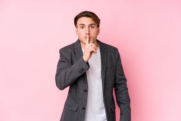 Młody caucasian biznesowego mężczyzna pozować odizolowywam utrzymujący sekret lub pytać o ciszę.