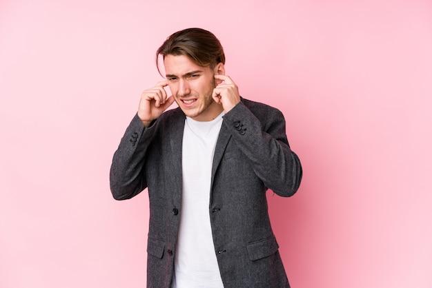 Młody caucasian biznesowy mężczyzna pozuje odosobnionych nakrywkowych ucho z rękami.
