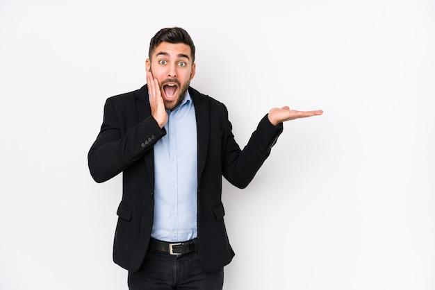 Młody caucasian biznesowy mężczyzna przeciw białej ścianie odizolowywającej trzyma kopii przestrzeń na palmie, utrzymuje oddawał policzek. zaskoczony i zachwycony.