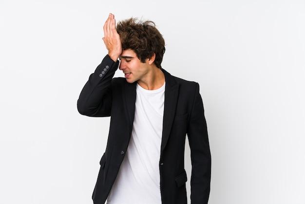 Młody caucasian biznesowy mężczyzna przeciw białej ścianie odizolowywał zapominać coś, uderzać czoło dłonią i zamykać oczy.