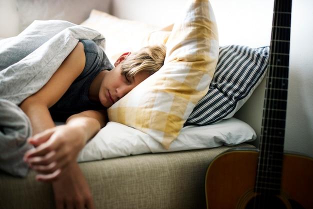 Młody caucasian chłopiec dosypianie w łóżku