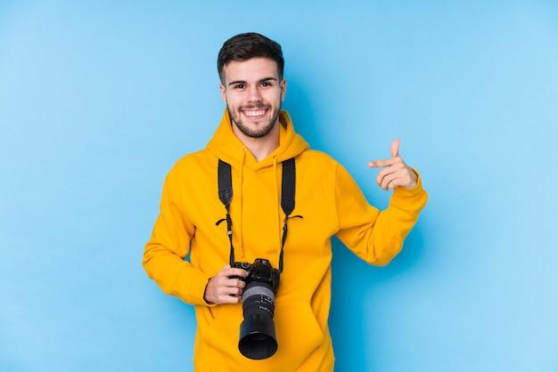Młody caucasian fotografa mężczyzna odizolowywał osoby wskazuje ręką do koszulowej kopii przestrzeni, dumny i ufny