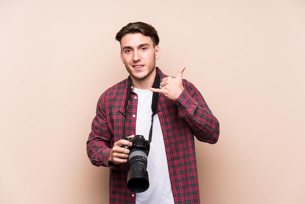 Młody caucasian fotografa mężczyzna odizolowywał pokazywać telefonu komórkowego wezwania gest z palcami.