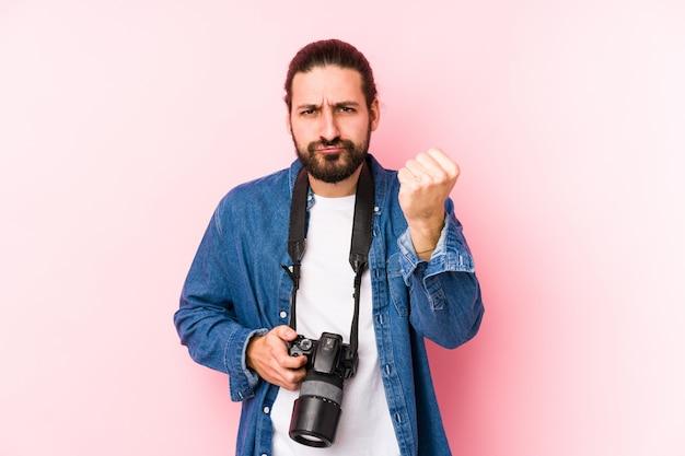 Młody caucasian fotografa mężczyzna pokazuje pięść kamera, agresywny wyraz twarzy.