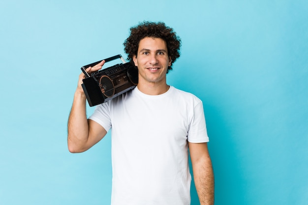 Młody caucasian kędzierzawy mężczyzna trzyma blaster guetto szczęśliwy, uśmiechnięty i wesoły.